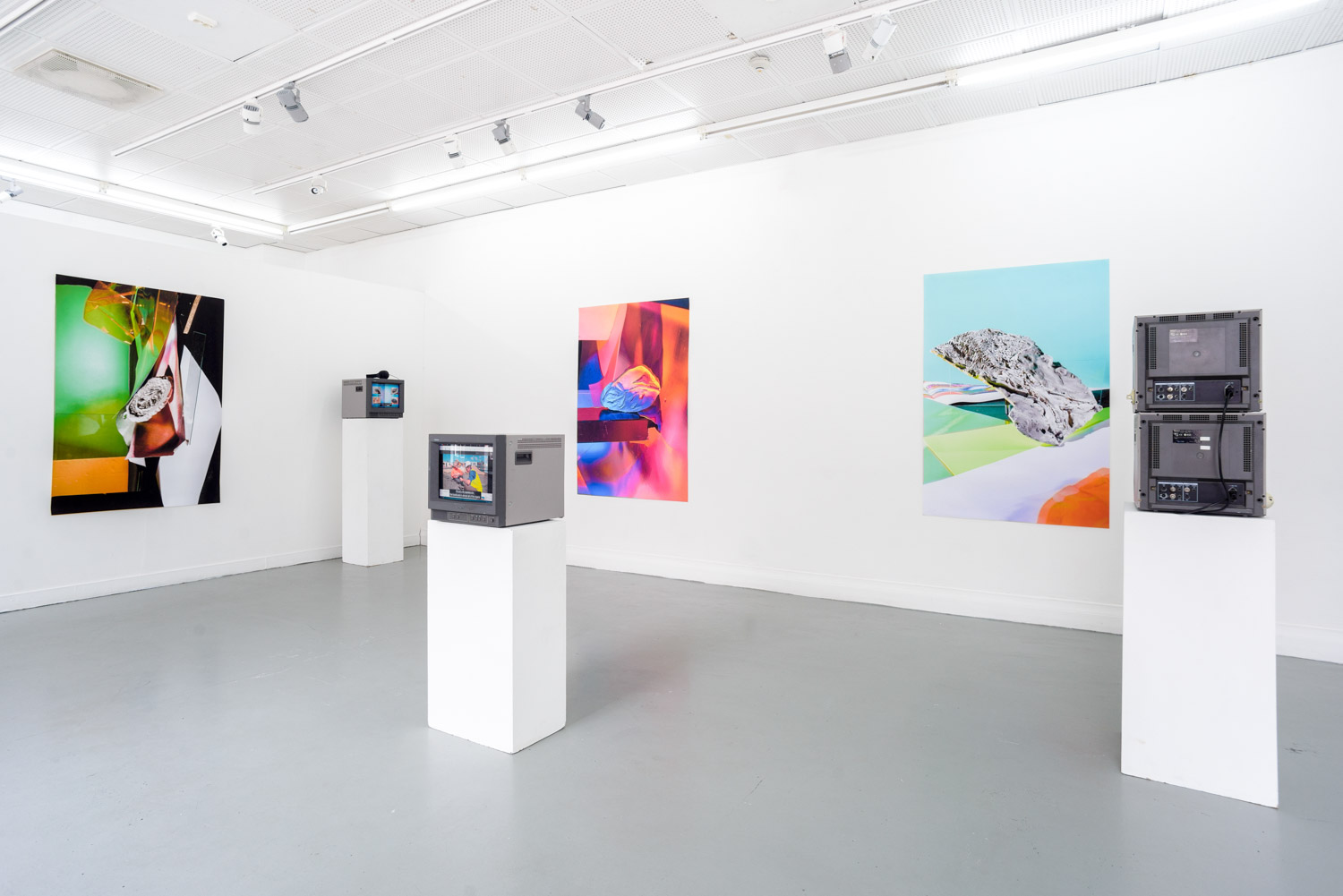 contemporary art installation in a white gallery with monitors on podiums and a frame on the wall by artist Stefano Conti