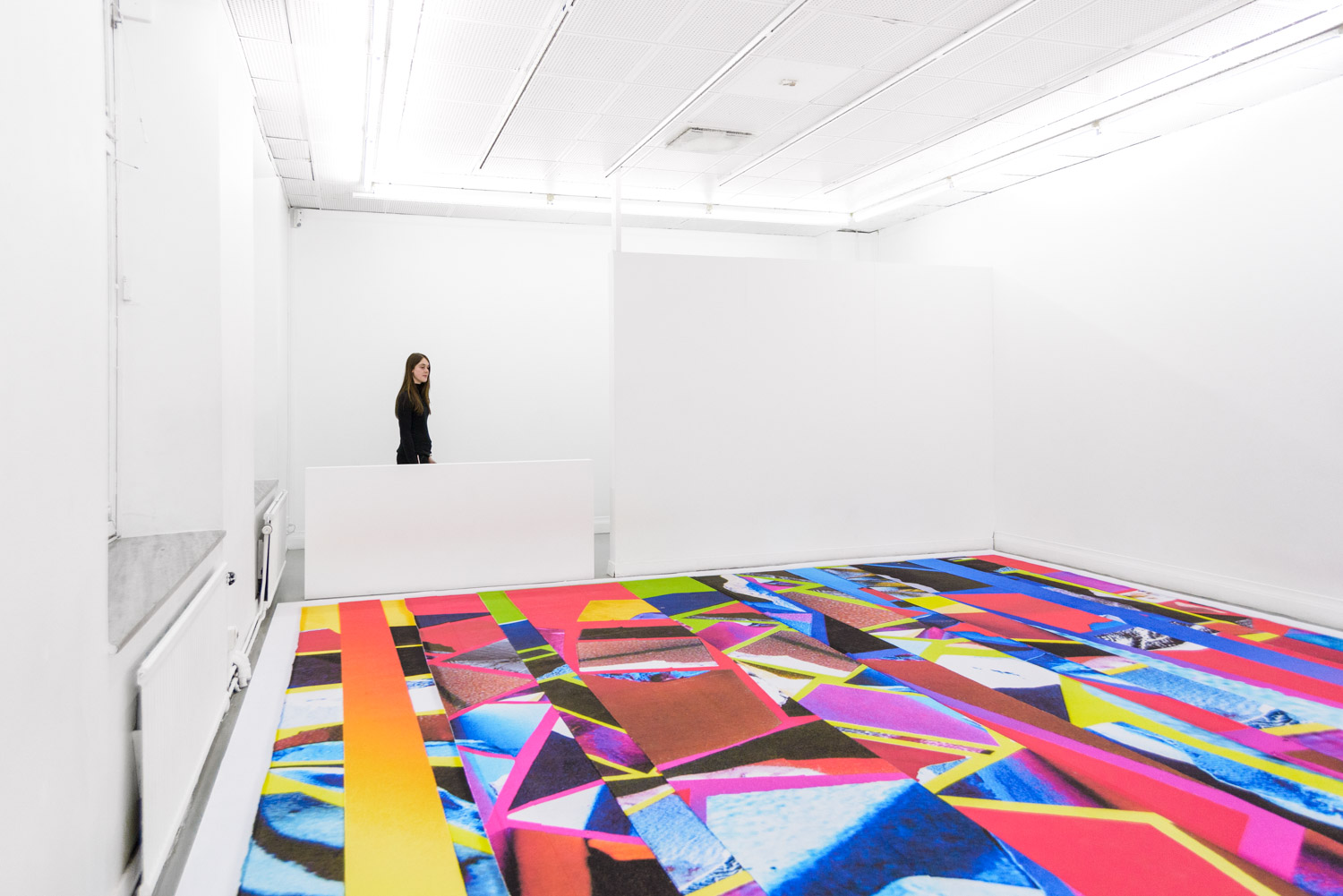 contemporary colorful carpet as an art installation by Stefano Conti in a white gallery, with a visitor.